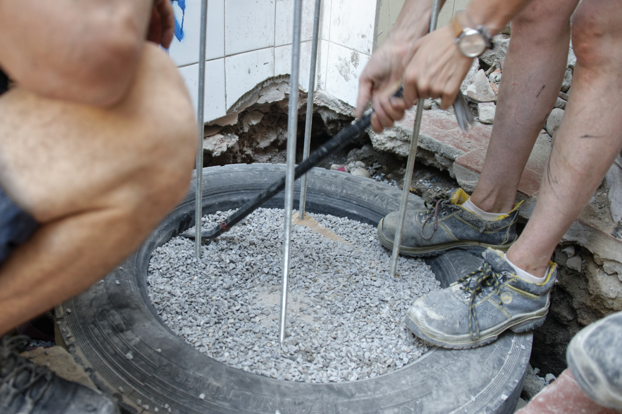 Filling a tyre with gravel.